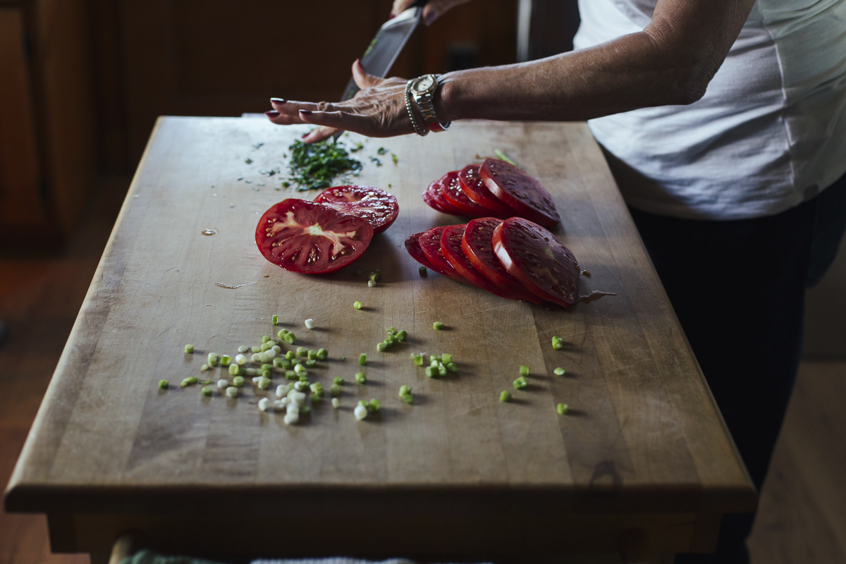 An older woman chops herbs to sprinkle on slided tomatoes sitting on a kitchen island.